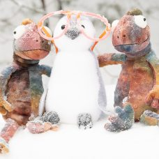 Kaksi kameleonttia ja pingviini lumella